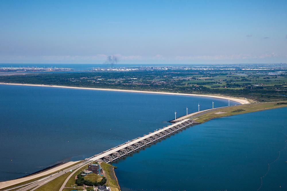 Nederland, Zuid-Holland, Haringvliet, 12-06-2009; Haringvlietsluizen en Haringvlietdam, gezien naar Rockanje op het eiland Voorne-Putten, onder in beeld de damaanzet op Goeree-Overflakkee. Aan de horizon Rotterdam Europoort. De sluizen, onderdeel van de Deltawerken, zijn spuisluizen en zorgen er voor dat het zoete water uit het Haringvliet (rechts op de foto) zoals aangevoerd door Maas en Rijn geloosd kan worden. In het kader van modern natuurbeheer  ('getemd getij') gaan de sluizen tegenwoordig bij eb én vloed beperkt open, om de getijden hun enigszin terug te laten komen in achterliggende estuarium .Dam and sluices between islands Voorne-Putten en Goeree-Overflakkee (bottom); the sluices are for draining water coming from the rivers Rhine and Maas (Meuse) from the natural bassin (right) to the North sea (left). Modern ecolical insight has led to opening the sluices semi-permanently, resulting in the estuary function of the Haringvliet patially being restored.Swart collectie, luchtfoto (25 procent toeslag); Swart Collection, aerial photo (additional fee required).foto Siebe Swart / photo Siebe Swart
