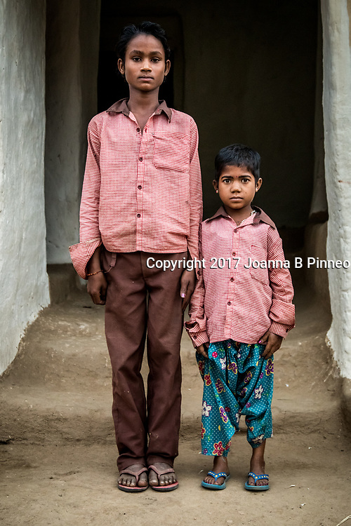Gariya, Sonbhadra, Uttar Pradesh, India<br /> Rina, age 13 (R) whose growth is stunted, stands next to her younger brother Mahendra, (L) age 11. Gariya, Sonbhadra.<br /> The health problems in the village started 20 years ago. Before that everyone was fine. It has just been getting worse for the last 10 years. Everyone reports having chest pain, chronic stomach pains, a lot of back pain, joint pains, pains in their knees. Water in this village tests high levels of fluoride in the water. A 2012 report by the Center for Science and Environment based in New Delhi sampled water, soil, cereals in the areas and villages around the reservoir. Most of the drinking water was found not suitable for drinking. A few of the towns that have water supplied by the companies or government are good. The results of the water, soil and fish sample testing indicate pollution due to mercury, arsenic, and fluoride.