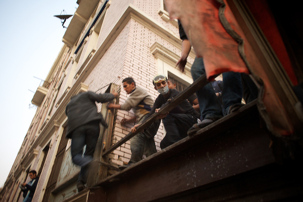 Egyptian men run for cover from an attack with rubber bullets and tear gas by the security forces in central Cairo.