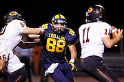 Milpitas High School defensive lineman Jason Scrempos (88) rushes Woodside quarterback Robert Wang (11) at Milpitas High School in Milpitas, California, on September 13, 2013. The Trojans went on to beat the Wildcats 50-6. (Stan Olszewski/SOSKIphoto)