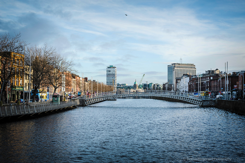 A view of the River Liffey in Winter, with people crossing the Ha'Penny Bridge, and bare trees on the banks of the Liffey