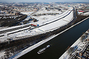 Nederland, Utrecht, Leidsche Rijn, 31-01-2010; binnenvaartschip op Amsterdam-Rijnkanaal met op het tweede plan de zuidelijke ingang van de nieuwe landtunnel voor de A2. De tunnel ligt parallel aan de bestaande A2, het asfalt zal op termijn verdwijnen en op het dak van de tunnel zal een park komen. Links van de tunnel Leidsche Rijn met de wijken Langerak en Parkwijk. .Barge on the  Amsterdam-Rhine Canal, on the the second plan the southern entrance of the new landtunnel for A2. The tunnel lies parallel to the existing motorway A2, the asphalt will eventually disappear and the roof of the tunnel will be a park. Left of the tunnel Leidsche Rijn with the districts and Langerak Parkwijk. .luchtfoto (toeslag), aerial photo (additional fee required).foto/photo Siebe Swart