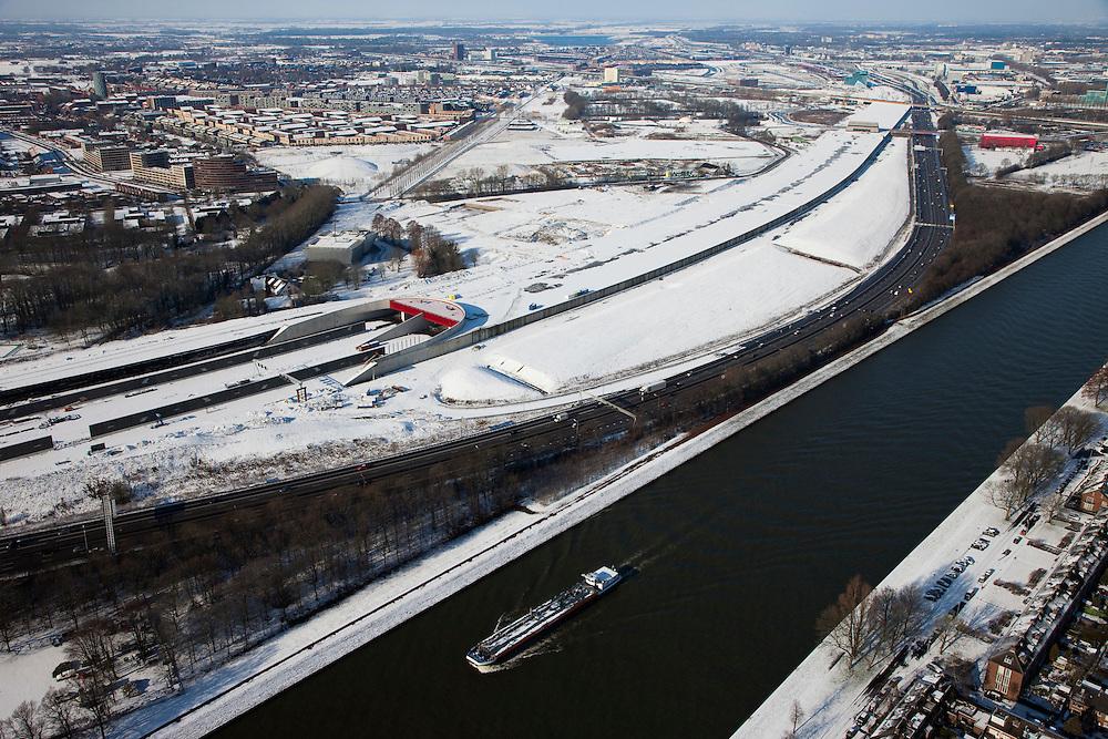 Nederland, Utrecht, Leidsche Rijn, 31-01-2010; binnenvaartschip op Amsterdam-Rijnkanaal met op het tweede plan de zuidelijke ingang van de nieuwe landtunnel voor de A2. De tunnel ligt parallel aan de bestaande A2, het asfalt zal op termijn verdwijnen en op het dak van de tunnel zal een park komen. Links van de tunnel Leidsche Rijn met de wijken Langerak en Parkwijk. .Barge on the  Amsterdam-Rhine Canal, on the the second plan the southern entrance of the new landtunnel for A2. The tunnel lies parallel to the existing motorway A2, the asphalt will eventually disappear and the roof of the tunnel will be a park. Left of the tunnel Leidsche Rijn with the districts and Langerak Parkwijk. .luchtfoto (toeslag), aerial photo (additional fee required).foto/photo Siebe Swart