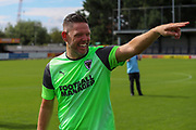 AFC Wimbledon goalkeeping coach Ashley Bayes pointing and laughing during the official team photocall for AFC Wimbledon at the Cherry Red Records Stadium, Kingston, England on 8 August 2019.