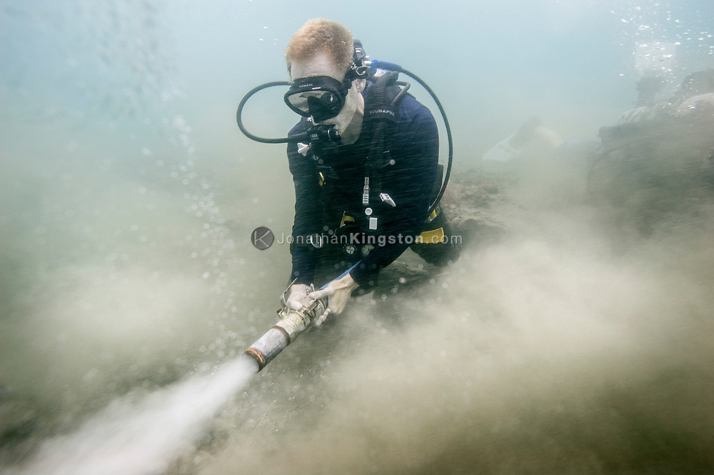 Graduate research assistant Jacob Hooge uses a water jet to push sand away from the wooden hull of the Encarnación, a cargo vessel that was part of the 17th century Spanish Tierra Firme fleet in Panama.