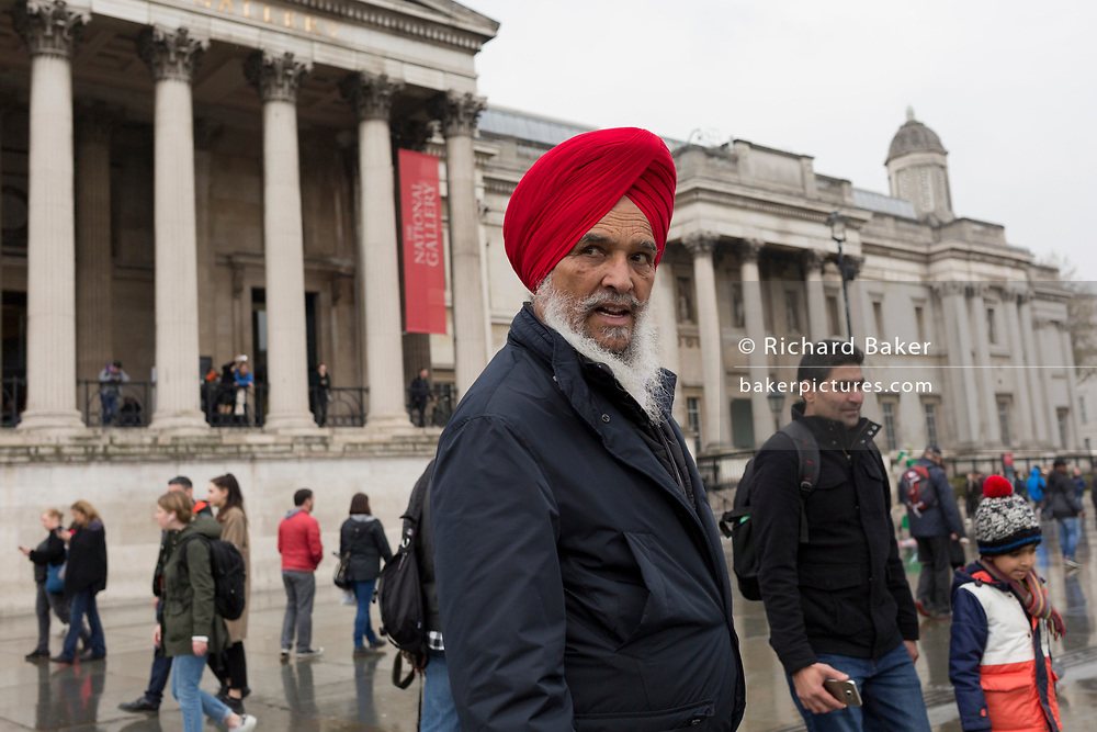 A Sikh man wearing a red turban voutside the columned architecture of the National Gallery during a visit to Trafalgar Square, Westminster, on 9th April 2019, in London, England.
