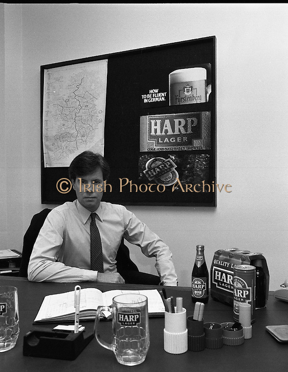 Mr John Lennon, Guinness.  (R91)..1988..21.11.1988..11.21.1988..21st November 1988..Mr John Lennon of Guinness Marketing Department was part of the new launch of Harp. Harp is a larger brewed by Guinness at its brewery at St James's gate, Dublin...Image shows Mr John Lennon, Guinness, Marketing Dept in his office for the promotion of Harp lager.