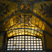Light shines through a window onto an ornately painted ceiling in Hagia Sophia. Originally built as a Christian cathedral, then converted to a Muslim mosque in the 15th century, and now a museum (since 1935), the Hagia Sophia is one of the oldest and grandest buildings in Istanbul. For a thousand years, it was the largest cathedral in the world and is regarded as the crowning achievement of Byzantine architecture.