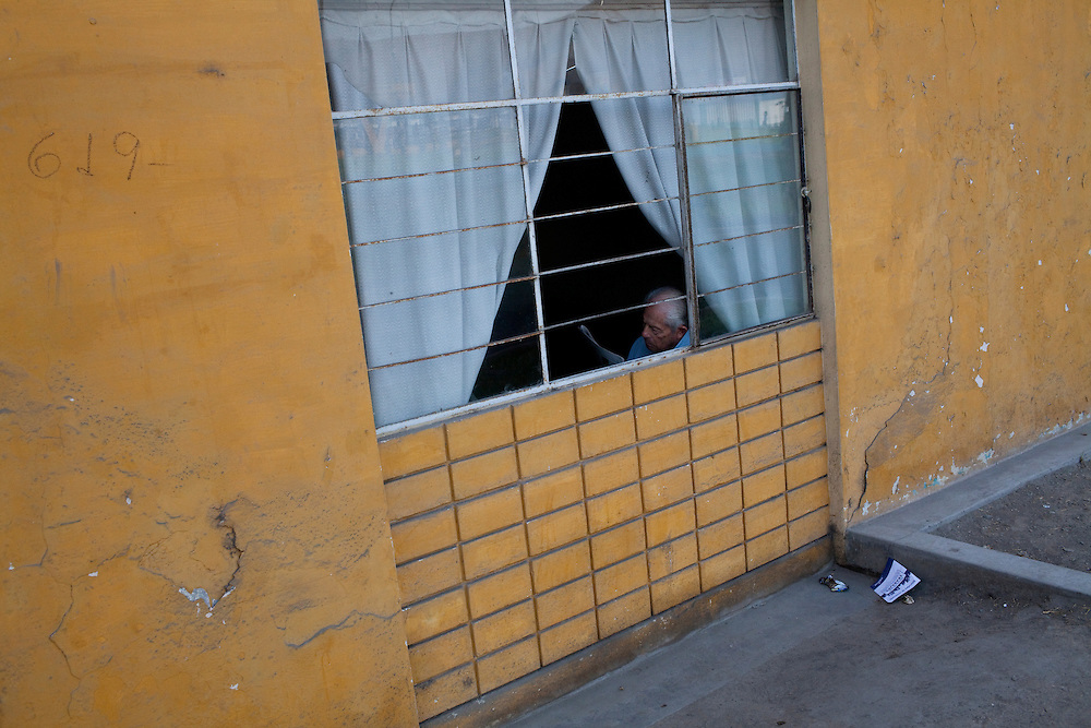 A man reads in a window on Saturday, Apr. 18, 2009 in Ventanilla, Peru.