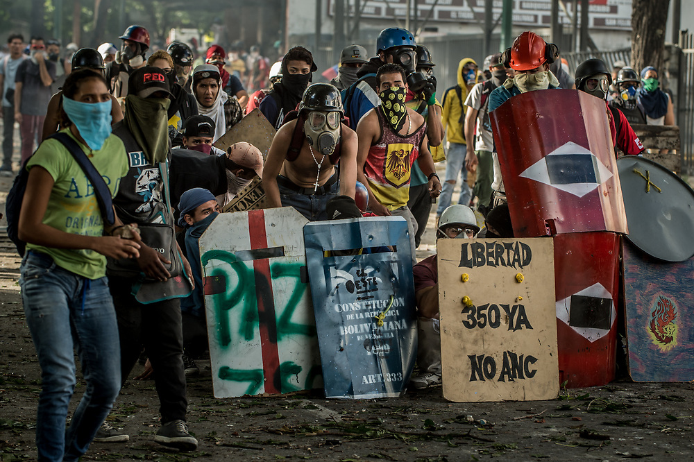 CARACAS, VENEZUELA - JULY 26, 2017: Members of La Resistencia take cover behind homemade shields during clashes with soldiers during an anti-government protest to demand that the National Constituent Assembly election scheduled for Sunday, July 30th be cancelled. The political opposition called for a 48 hour national strike on July 26th and 27th, and for their supporters to close businesses, not go to work, and instead create barricades to block off their streets.  Opposition controlled areas of the country were completely shut down.  The strike was called as part of the opposition's civil resistance movement - that began on April 1st, to protest against the Socialist government's attempt to elect a new assembly that will have the power to re-write the constitution, and their opposition to the Socialist's continued threats to Venezuelan Democracy.  PHOTO: Meridith Kohut for The New York Times