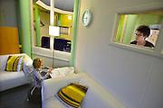 Nederland, Nijmegen, 14-2-2014Logeerhuis, weekendopvang, kinderhotel, voor kinderen met een psychische stoornis, vooral autisme. Het kleine meisje op de foto is Luna. Ze tekent een regenboog. Nadat de kinderen aangekomen zijn vertrekken de ouders en nemen de begeleiders het over. Vanuit de keuken is zicht op de woonkamer.Foto: Flip Franssen