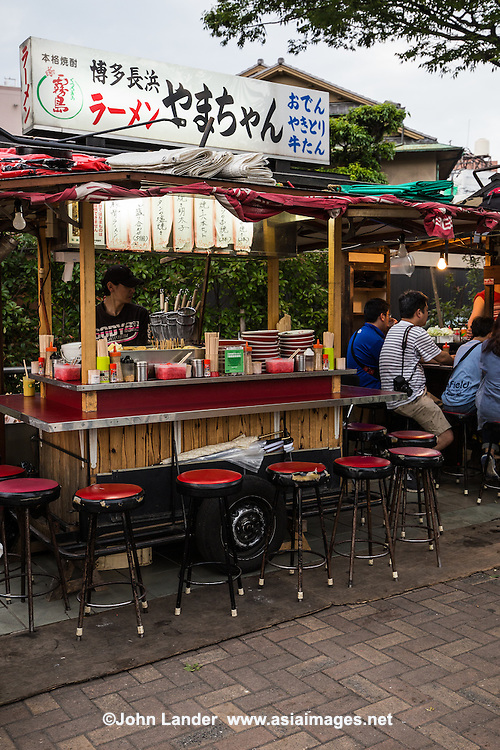 "A yatai is a small, mobile food stall typically selling ramen, yakitori or oden. The name literally means ""shop stand."" The stall is set up in the early evening on sidewalks and removed late at night or in the early morning hours. Beer, sake and shochu are usually available. A salaryman might relax with colleagues over dinner and drinks at a yatai on his way home from work. Fukuoka is well known in Japan for keeping the yatai tradition alive."