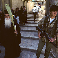 Israel, Jerusalem, Greek Orthodox priest walks past Israeli soldier outside Church of the Holy Sepulcher on Palm Sunday
