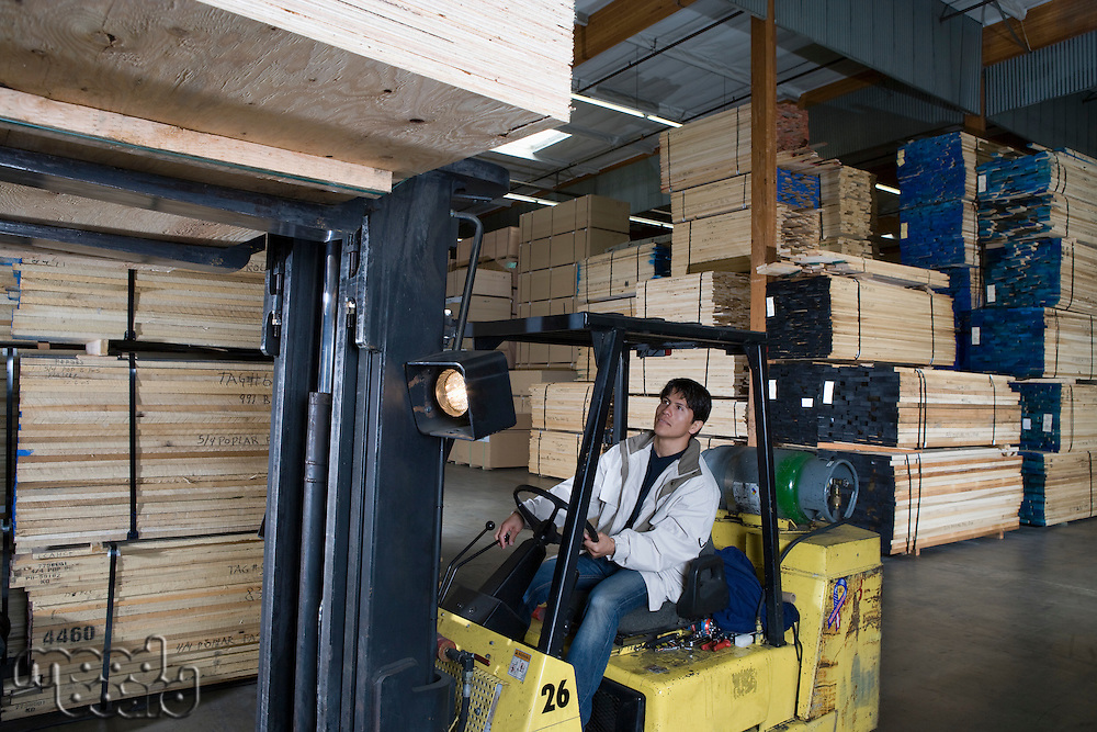 Mid-adult man driving forklift truck