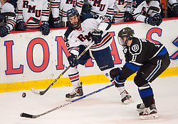 March 11 2016: Robert Morris Colonials forward Daniel Leavens (26) chips the puck past Bentley Falcons forward Tyler Deresky (11) during the first period in game one of the Atlantic Hockey quarterfinals series between the Bentley Falcons and the Robert Morris Colonials at the 84 Lumber Arena in Neville Island, Pennsylvania (Photo by Justin Berl)