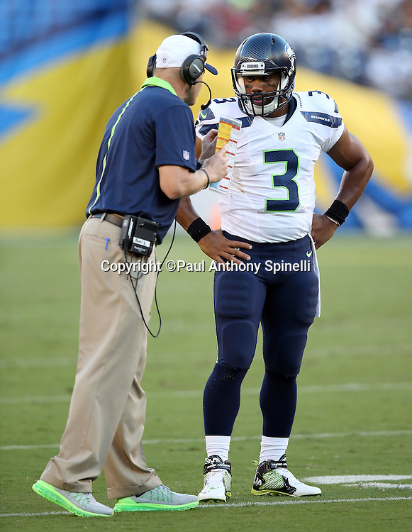 Seattle Seahawks offensive coordinator Darrell Bevell talks strategy with Seattle Seahawks quarterback Russell Wilson (3) during a break in the action at the 2015 NFL preseason football game against the San Diego Chargers on Saturday, Aug. 29, 2015 in San Diego. The Seahawks won the game 16-15. (©Paul Anthony Spinelli)