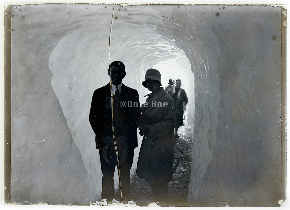 people posing inside ice glacier tunnel 1900s
