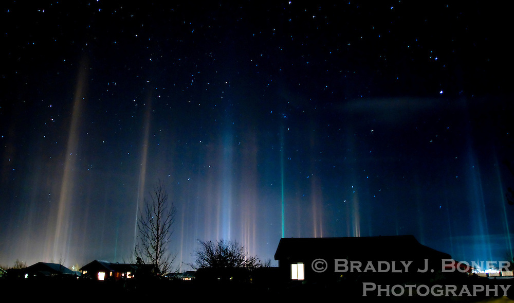 "A phenomenon known as ""light pillars"" spreads across the night sky over Victor, Idaho. The colorful columns form when light from the ground reflects off flat snow crystals descending through very cold air."