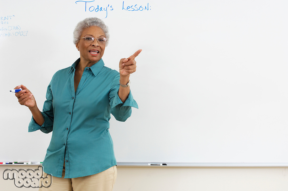 Female teacher pointing by whiteboard in classroom