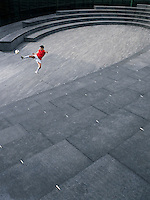 Man kicking soccer ball in the Scoop amphitheatre London England elevated view