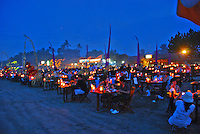 Lovely scene of gaily lit diners at night on a beach in Jimbaran, Bali, Indonesia.
