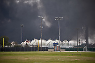 Plume from the Texas Petroleum Chemical  plant, that was still on fire the day after multiple explosions rocked the plant,  next to tennis courts adjacent to the plant. Though authorities issued a mandatory evacation for those living in a four mile radious of the plant, many remained at home.  Regualtors warned that its air monitoring indicates no human health concerns, though the incident is causing the release of chemicals called volatile organic compounds (VOCs) and that elevated levels of VOCs from this facility are odorous. Short-term exposure to high concentrations of VOCs can cause eye, nose, and throat irritation, shortness of breath, headaches, and nausea.