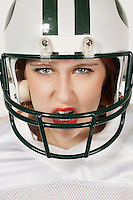 Portrait of an aggressive young woman in football uniform against gray background