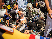 26 DECEMBER 2013 - BANGKOK, THAILAND:  Anti-government protestors try to help one of their supporters who was shot with a rubber bullet by Thai riot police. Thousands of anti-government protestors flooded into the area around the Thai Japan Stadium to try to prevent the drawing of ballot list numbers by the Election Commission, which determines the order in which candidates appear on the ballot of the Feb. 2 election. They were unable to break into the stadium and ballot list draw went as scheduled. The protestors then started throwing rocks and small explosives at police who responded with tear gas and rubber bullets. At least 20 people were hospitalized in the melee and one policeman was reportedly shot by anti-government protestors.     PHOTO BY JACK KURTZ
