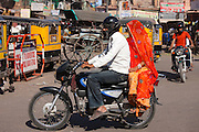 Indian couple riding motorcycle, street scene at Sardar Market at Girdikot, Jodhpur, Rajasthan, Northern India