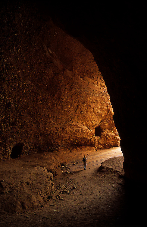 The photographer stares into the light from the darkness of the cave known as La Cuevona (the  big cave) in Las Medulas, Spain