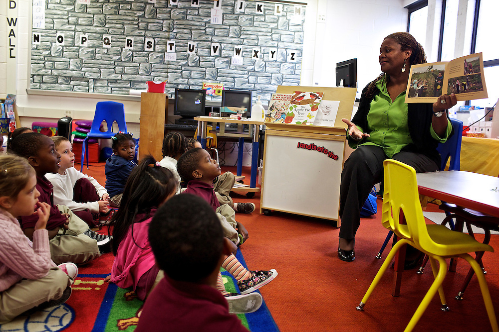 """Pre-kindergarten students at Calvin Rodwell Elementary School No. 256 in Baltimore, MD, listen to their teacher Erika Parker, right, as they read the book """"A Day at the Pumpkin Patch,"""" a non-fiction children's book about visiting a farm. The book was part of a """"Common Core"""" reading and learning unit, which aims to follow up non-fiction reading with learning in the field. The day after the children read the book about the farm, they visited Summers Farm in Frederick, MD."""