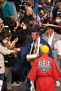 A Shinto priest passing out salt to onlookers ahead of the procession in the Tagata Fertility Festival.