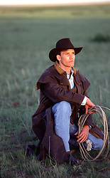cowboy with a lasso kneeling in a field