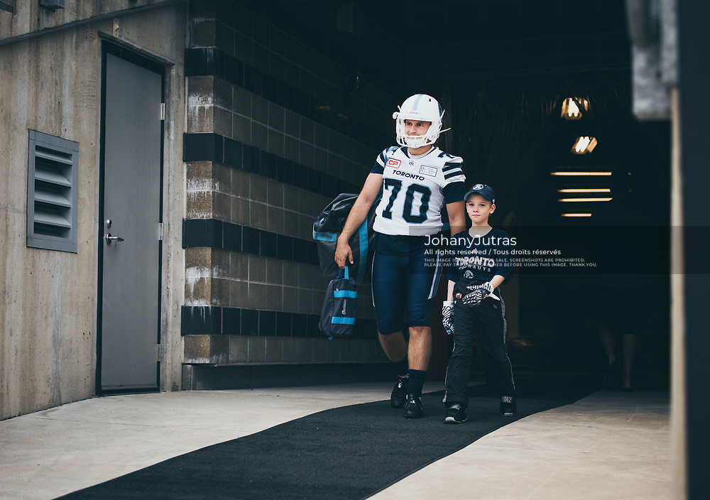 Lirim Hajrullahu (70) of the Toronto Argonauts and receivers coach Tommy Condell's son Luke before the Labour Day Classic game against the Hamilton Tiger-Cats at Tim Hortons Field in Hamilton ON, Monday September 4, 2017. (Photo: Johany Jutras)