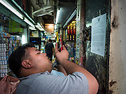 29 SEPTEMBER 2015 - BANGKOK, THAILAND:  A man uses his smart phone to photograph a flyer announcing the closure of Saphan Lek market in Bangkok. Street vendors and illegal market vendors in the Saphan Lek area will be removed in the next two weeks as a part of an urban renewal project coordinated by the Bangkok Metropolitan Administration. About 500 vendors along Damrongsathit Bridge, popularly known as Saphan Lek, have 15 days to relocate. Vendors who don't move will be evicted. Saphan Lek is just one of several markets and street vending areas being closed in Bangkok this year. The market is known for toy and replica guns, bootleg and pirated DVDs and CDs and electronic toys.   PHOTO BY JACK KURTZ