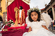 A young girl dressed as an angel sits on a truck in a religious procession from the Parroquia de San Miguel Arcangel church at the start of the week long fiesta of the patron saint Saint Michael September 21, 2017 in San Miguel de Allende, Mexico.