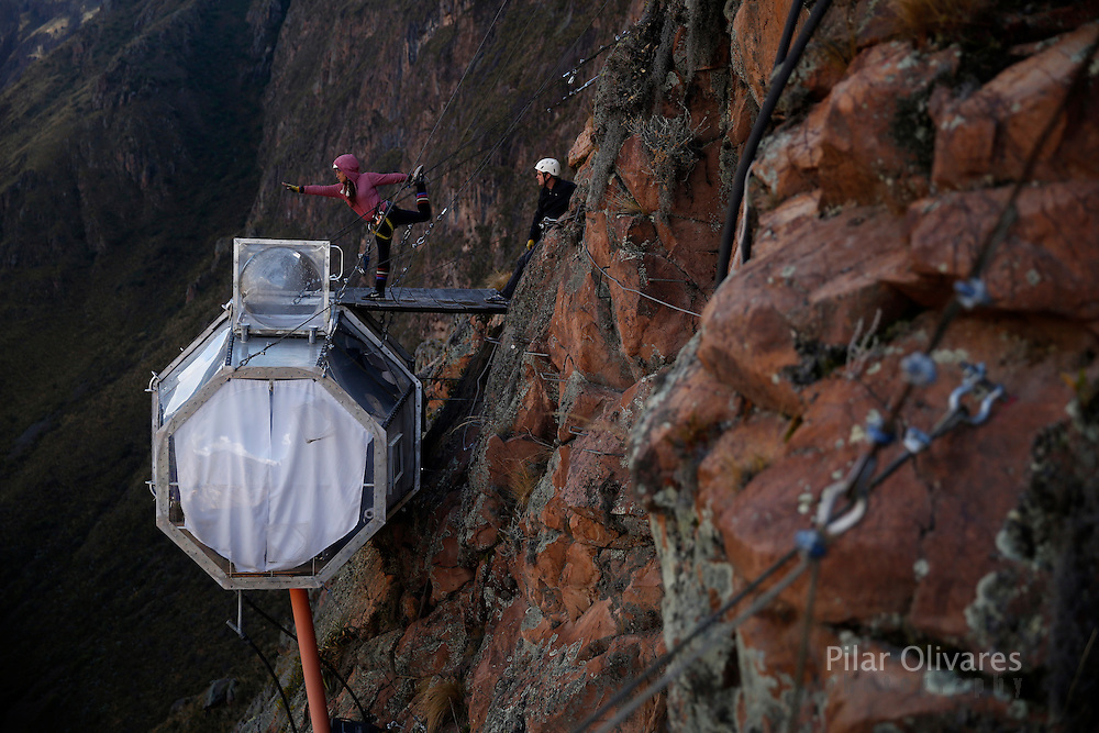A guest performs yoga above a cabine at the Skylodge Adventure Suites in the Sacred Valley in Cuzco, Peru, August 14, 2015. The Skylodge is composed by three capsule suites hanging at the top of the 1300 feet mountain with a 300 degree view of the Valley. To sleep at Skylodge, people must climb 400 meters of Via Ferrata path and to leave the hotel people go down  a trail through ziplines. REUTERS/Pilar Olivares