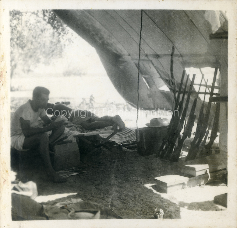 "The ""within tent ""pic is also Bagura nov 53. I told you Lyn Andrado who was our ""director"" was a surveyor so he brought the Survey Dept ïssue ""tent—very high quality as surveyors lived under canvas on occasion for months at a time. The tents comprised an inner & outer fly & Lance is sitting in the outer –we took two inners for sleeping & one outer for eating etc. Usually the outer fly goes over the inner for added insulation & weatherproofing."""