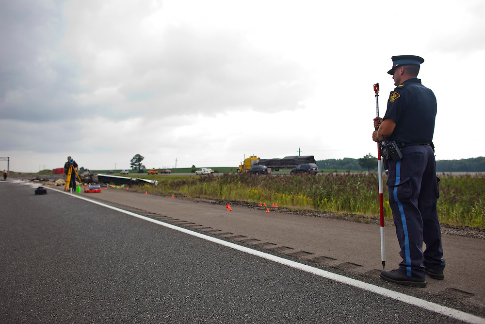 London, Ontario ---10-08-22--- Ontario Provincial police investigate the crash of a bus on the 401 highway near Woodstock, Ontario August 22, 2010. The crash which occurred about 6am left one person dead and sent 12 to hospital and left the highway closed for the morning.<br /> GEOFF ROBINS The Globe and Mail