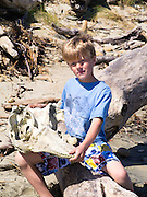 A boy sits with a bleached, decaying skull of a (likely) long-finned pilot whale (Globicephala melas) found on the beach at Mason Bay, Stewart Island (Rakiura), New Zealand.