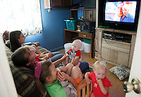 "Jeub family members watch the Steve Martin movie ""Cheaper By The Dozen"" (2003) about a man with 12 children at the family home in Monument, Colorado July 17, 2009. (L-R) Tabitha, 9; Havilah, 3; Hannah, 6; Keilah, 8; Cynthia; Josiah, 5; Noah, 10. Quiverfull believers Wendy and Chris Jeub have 15 children and would be happy to have more if God wills it they say. Two of the 15 children have moved out. Picture taken July 17, 2009.  REUTERS/Rick Wilking (UNITED STATES SOCIETY RELIGION)"