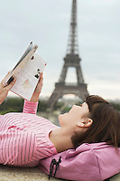 France Paris Young woman reading book on balcony with Eiffel Tower in distance