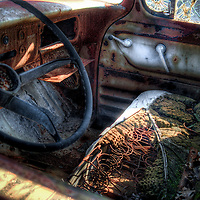 A wrecked old car with driving wheel and broken seat