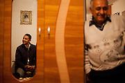Father Gheorghe Budrega of 22 years old Roma student Cornelia Budrega in his house. In the mirror Roma activist Marius Tudor.