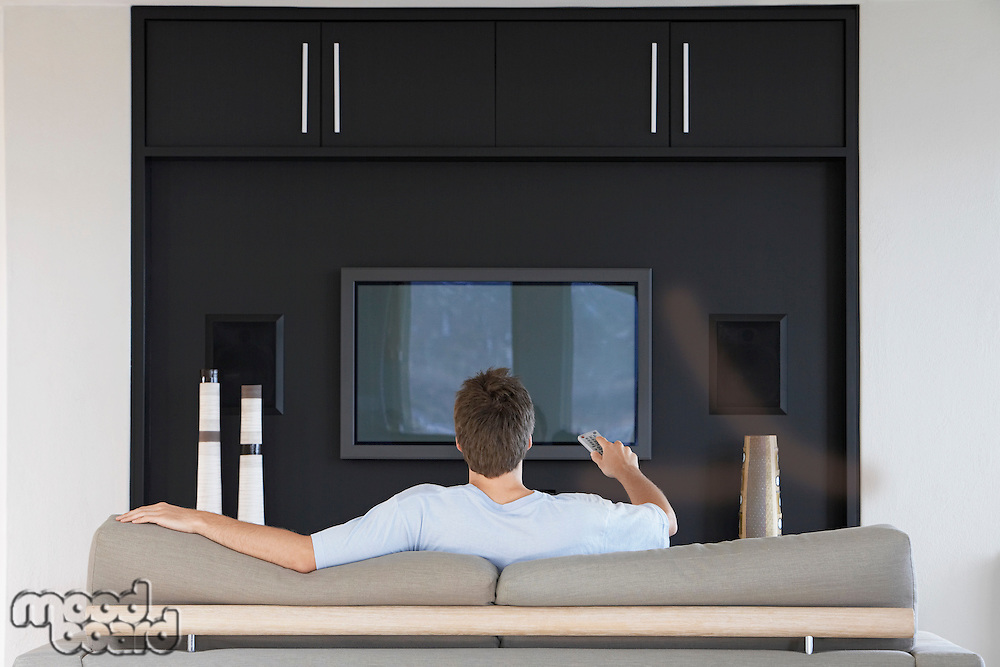 Man using remote control sitting in front of flat screen television back view