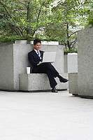 China Hong Kong business man sitting on stone bench using laptop