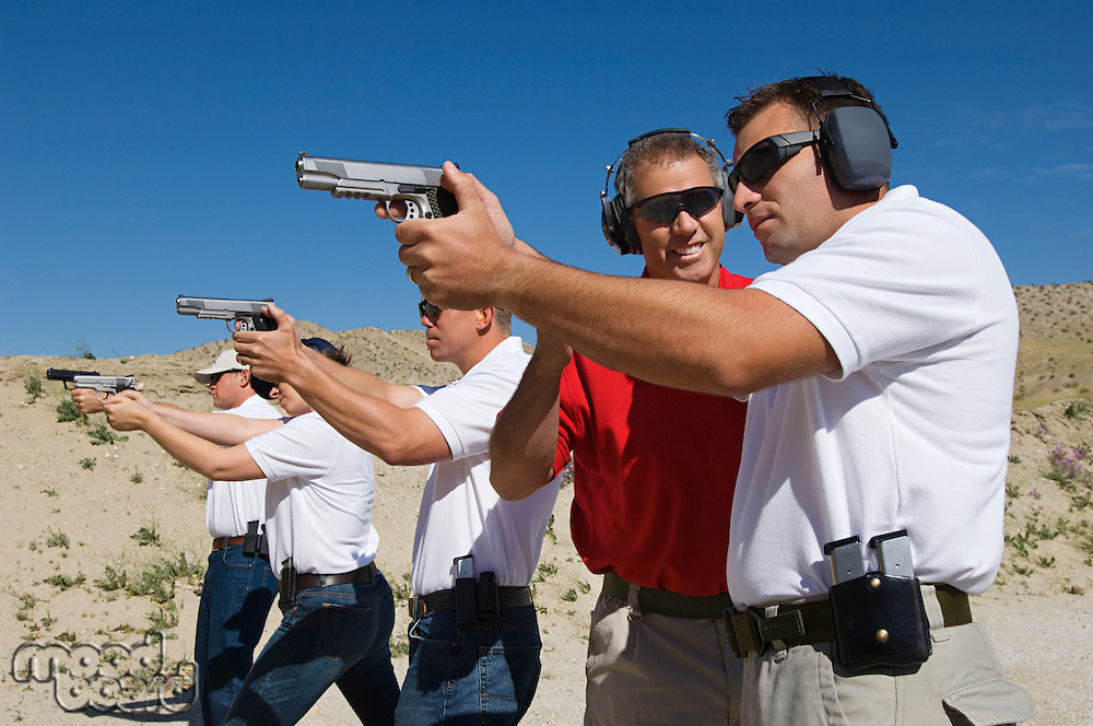 Instructor assisting men aiming hand guns at firing range