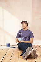 Man sitting on floor of unrenovated room holding coffee mug