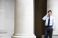 Businessman talking on cell phone by building pillar
