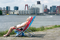 Nederland Rotterdam 31-05-2009 20090531 Foto: David Rozing .                                                                                    .Vrouw geniet van zomerweer langs de rivier de Maas, op de achtergrond de skyline van Rotterdam centrum                              .Woman enjoying sunny weather          .Holland, The Netherlands, dutch, Pays Bas, Europe ..Foto: David Rozing